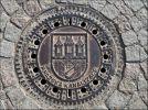 """Прага. Крышка люка. Надпись - """"Пражская канализация"""". Фрагменты пражского герба:  щит, на нём крепостная стена и открытые ворота; из ворот  выступает рука в доспехах, которая держит меч; три  башни."""