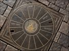 """Эйлат. Крышка люка. Башня с надписью """"Эйлат"""",  якорь, опускающийся в волны и солцне над морем - это герб Эйлата. Надпись справа - """"освещение"""", слева - """"коммуникации"""", снизу - """"Муниципалитет Эйлата"""""""